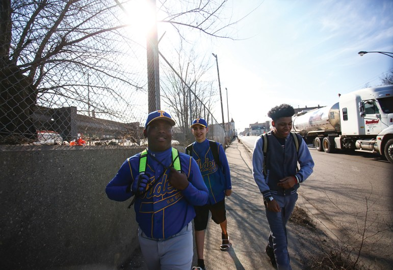 Tilden Blue Devils (from left) Lenord Davis, Christian Ruiz and Shanon Quantez walk from Tilden to their home field, Fuller Park, about six blocks away. Only a third of CPS baseball teams have a diamond on campus.