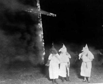 Ku Klux Klan members and a burning cross, Denver, Colorado, 1921.