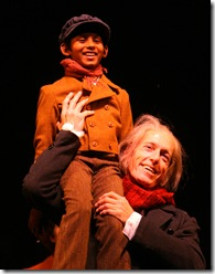 """Tiny Tim (Roni Akurati) proclaims, """"God bless us everyone!"""" on the shoulders of Ebenezer Scrooge (Larry Yando), in the 34th annual production of Goodman Theatre's A Christmas Carol."""