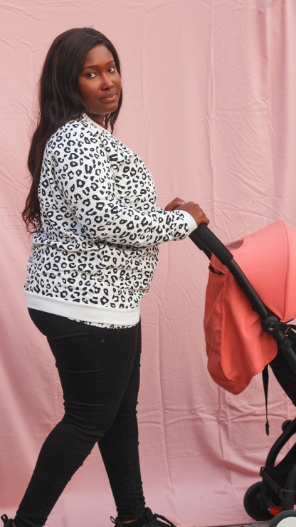 Mother wearing a breastfeeding jumper which is black and white leopard print pushing her baby in a pushchair.