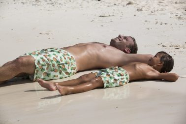 Father and son laying on the beach in Curacao