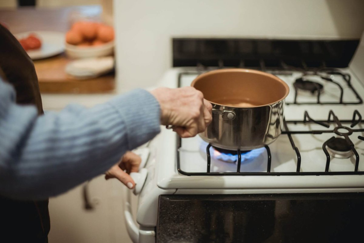 crop unrecognizable housewife placing saucepan on burning stove