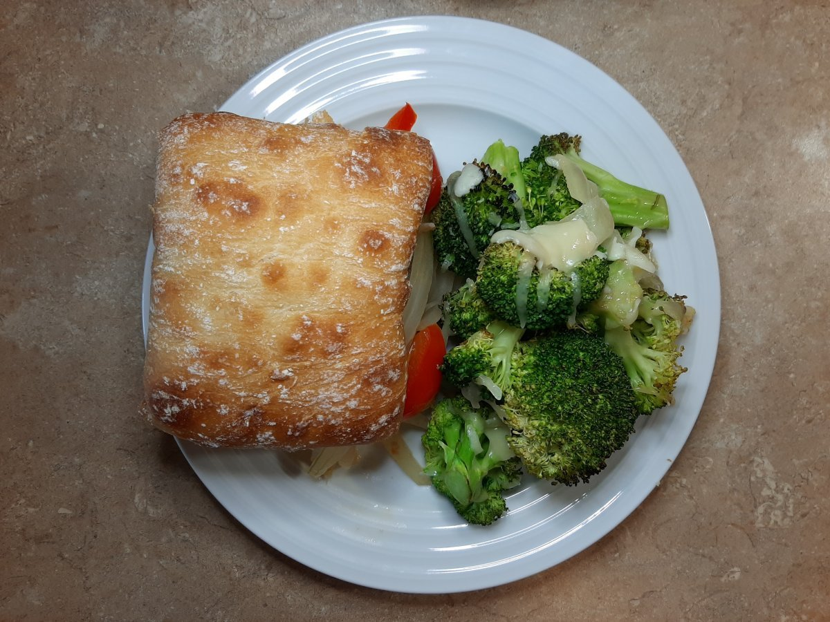 Italian sausage sandwich with a side of oven roasted broccoli with cheese