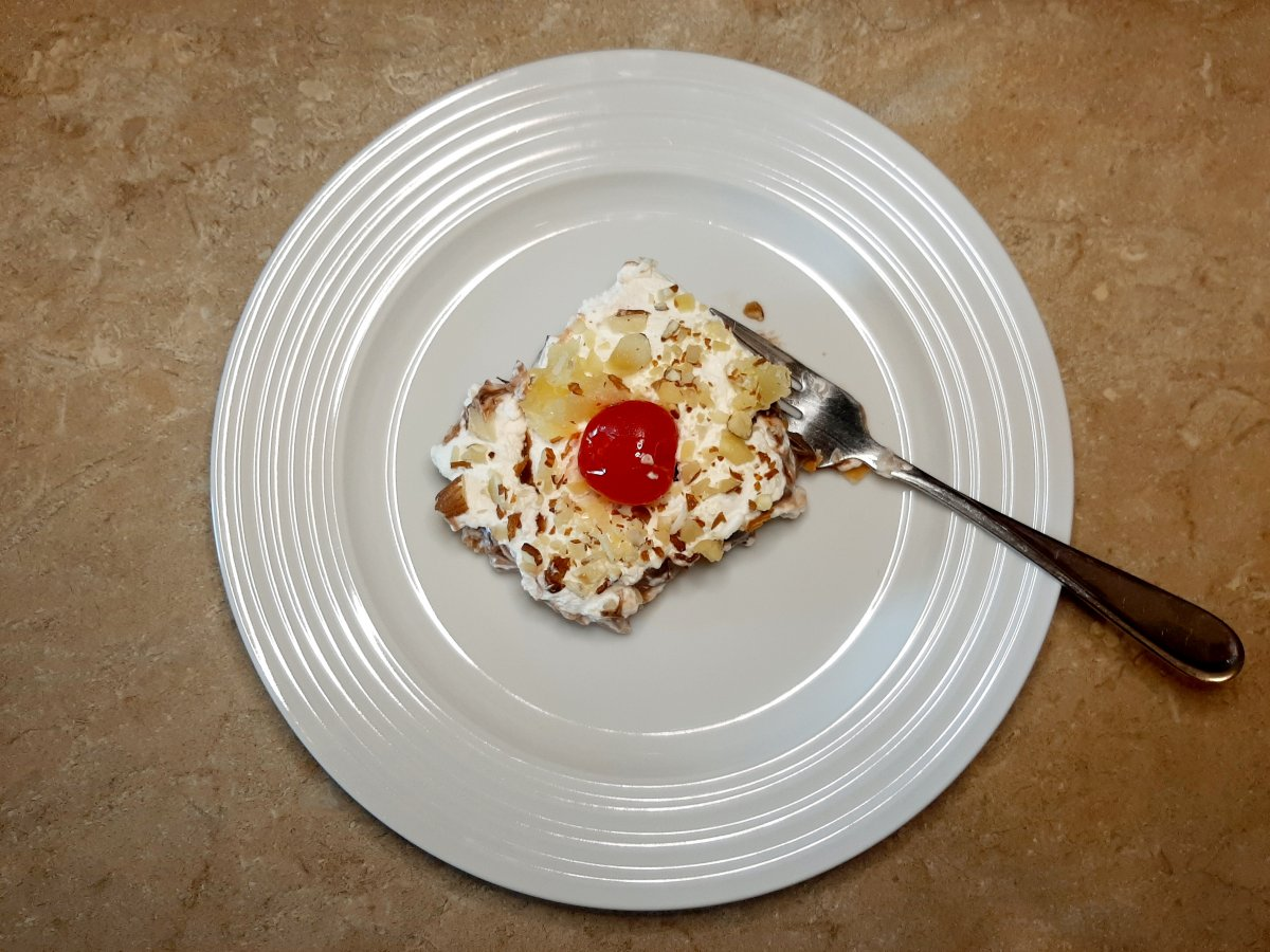 slice of banana pineapple dessert with whipped cream, pineapple, and a cherry