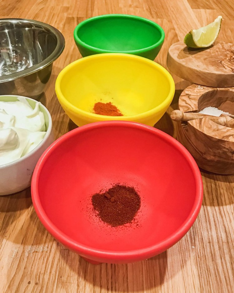 Multicolored bowls with chipotle powder, chili powder, smoked spanish paprika, a salt cellar, sour cream, and a mixing bowl all presented mis en place.