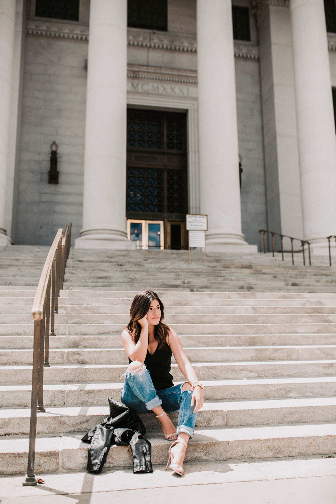 Carolina Hellal of Chic Talk wearing a black Bailey 44 top , American Eagle jeans, and Sam Edelman beige strap sandals