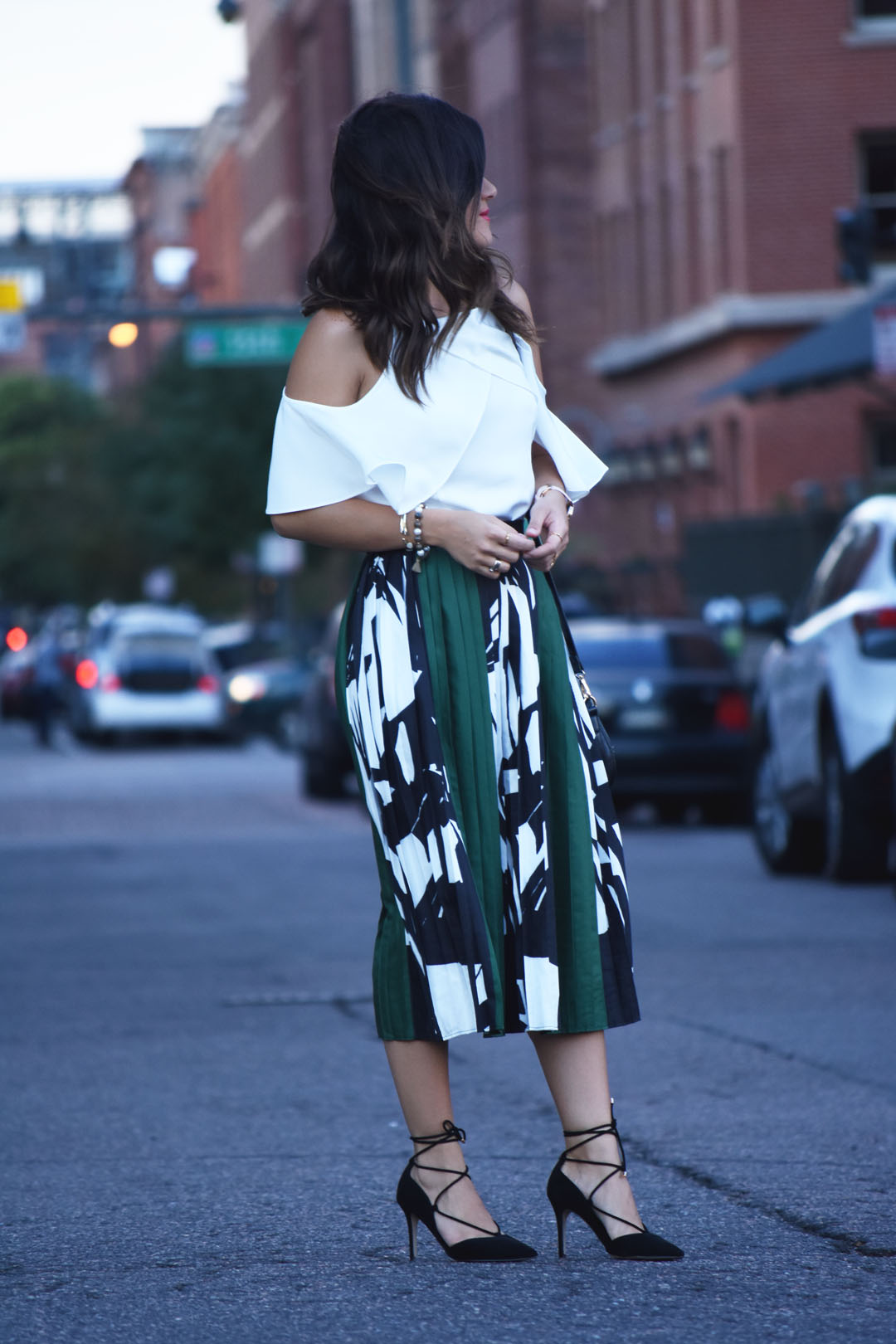 Carolina Hellal of Chic Talk wearing a pleated green skirt and cold shoulder top