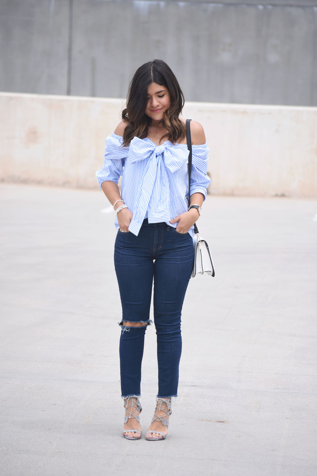 Carolina Hellal of the fashion blog Chic Talk wearing a SheIn tie front off the shoulders blouse, Madewell ripped jeans, and Public Desire grey sandals