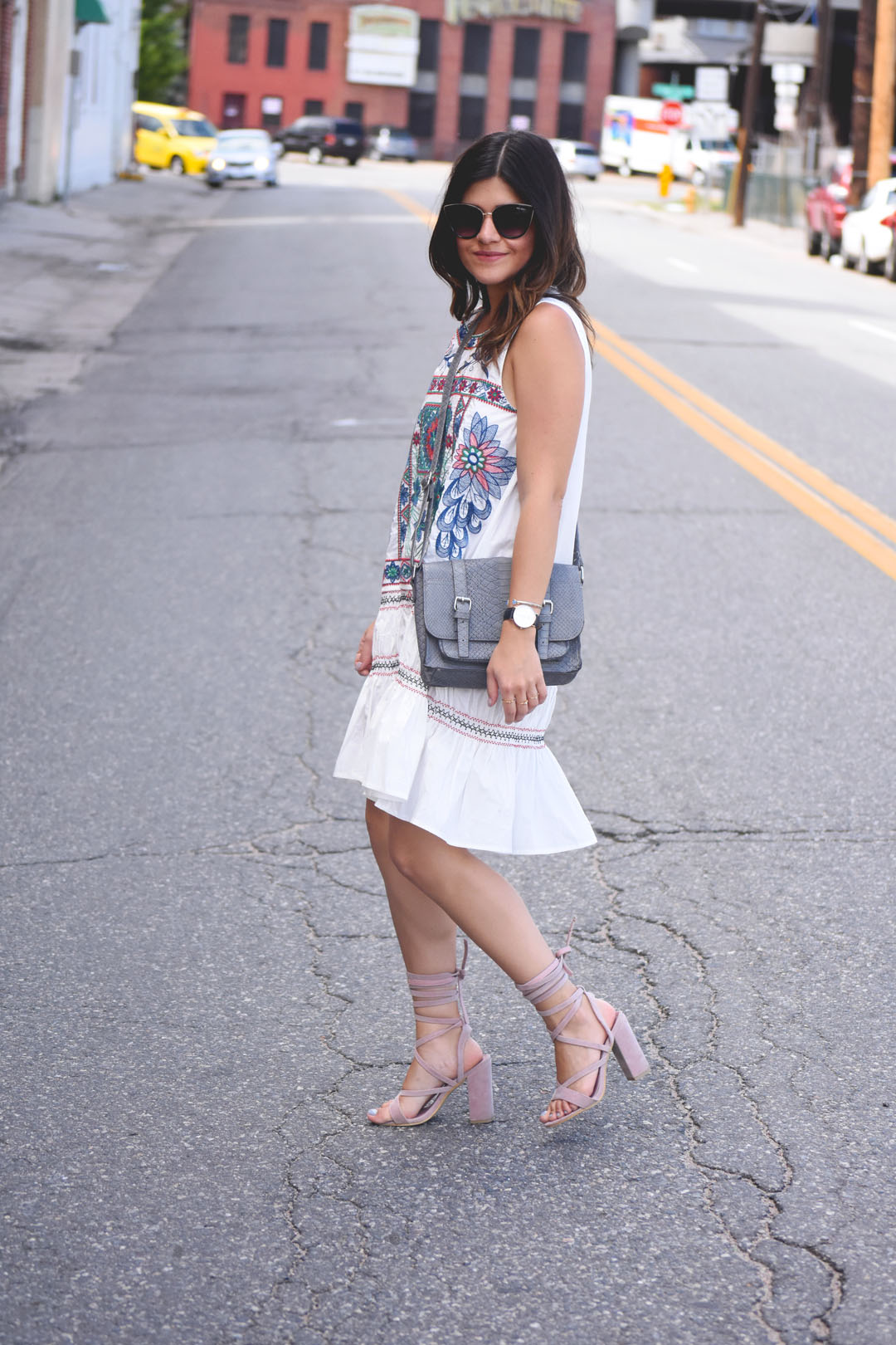 Carolina Hellal of the fashion blog Chic Talk wearing a Chicwish white summer dress, grey crossbody bag and Public Desire baby pink lace up sandals