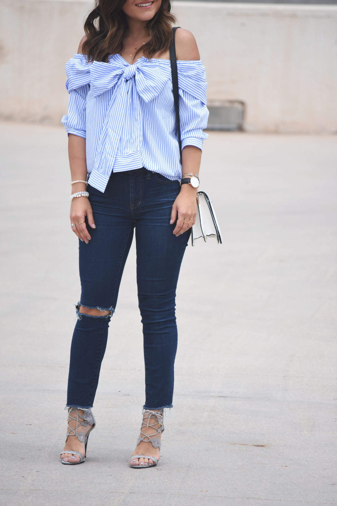 Carolina Hellal of the fashion blog Chic Talk wearing a casual look with a SheIn off the shoulder top and Madewell ripped jeans