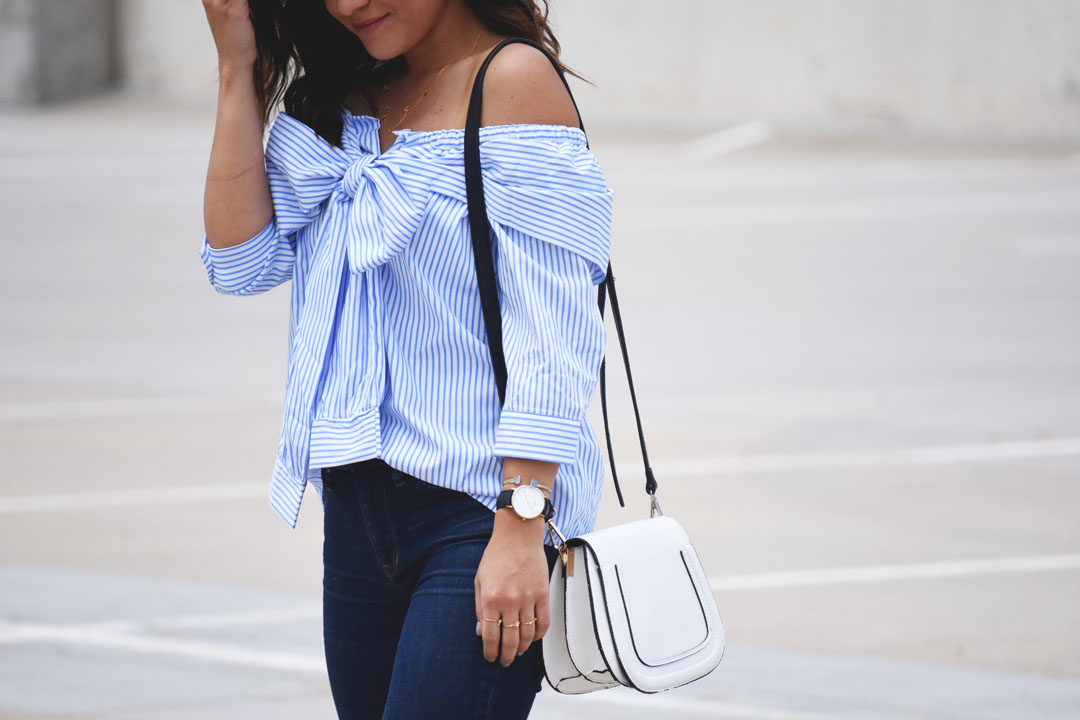 Carolina Hellal of Chic Talk wearing a SheIn blue striped off the shoulder top and a Solesociety white crossbody bag