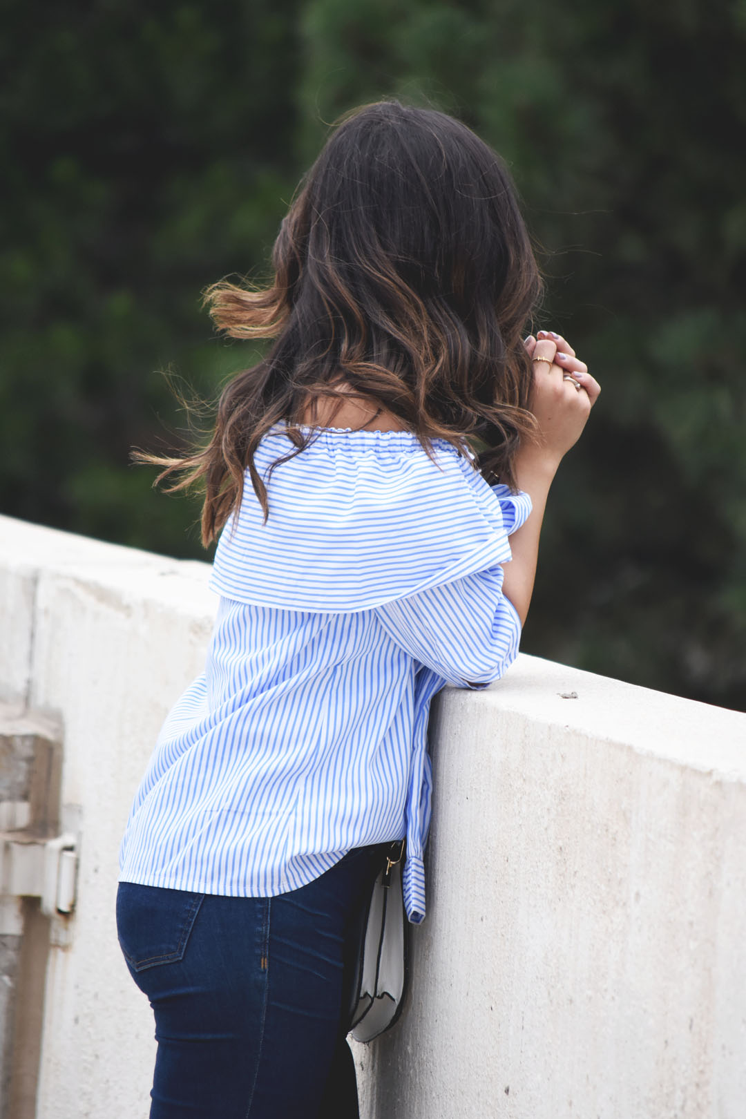 Carolina Hella of Chic Talk wearing an SheInside off the shoulder blue striped top and Madewell jeans