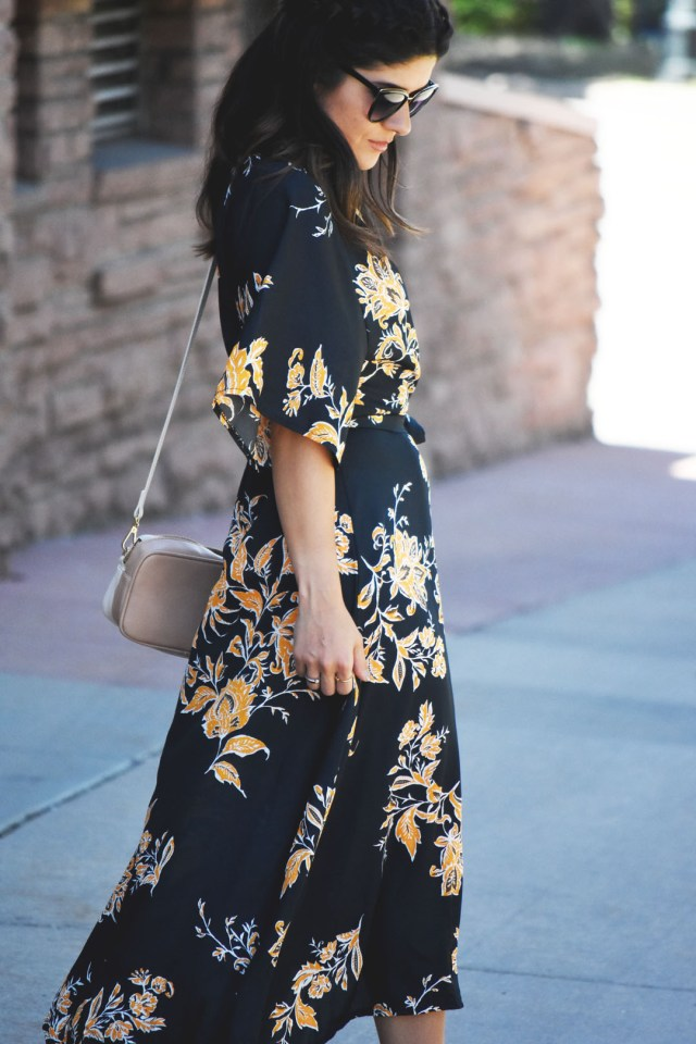 Carolina Hellal of Chic Talk wearing a floral wrap maxi dress, Nordstrom sunglasses, and Pueblo L.A dainty gold rings.