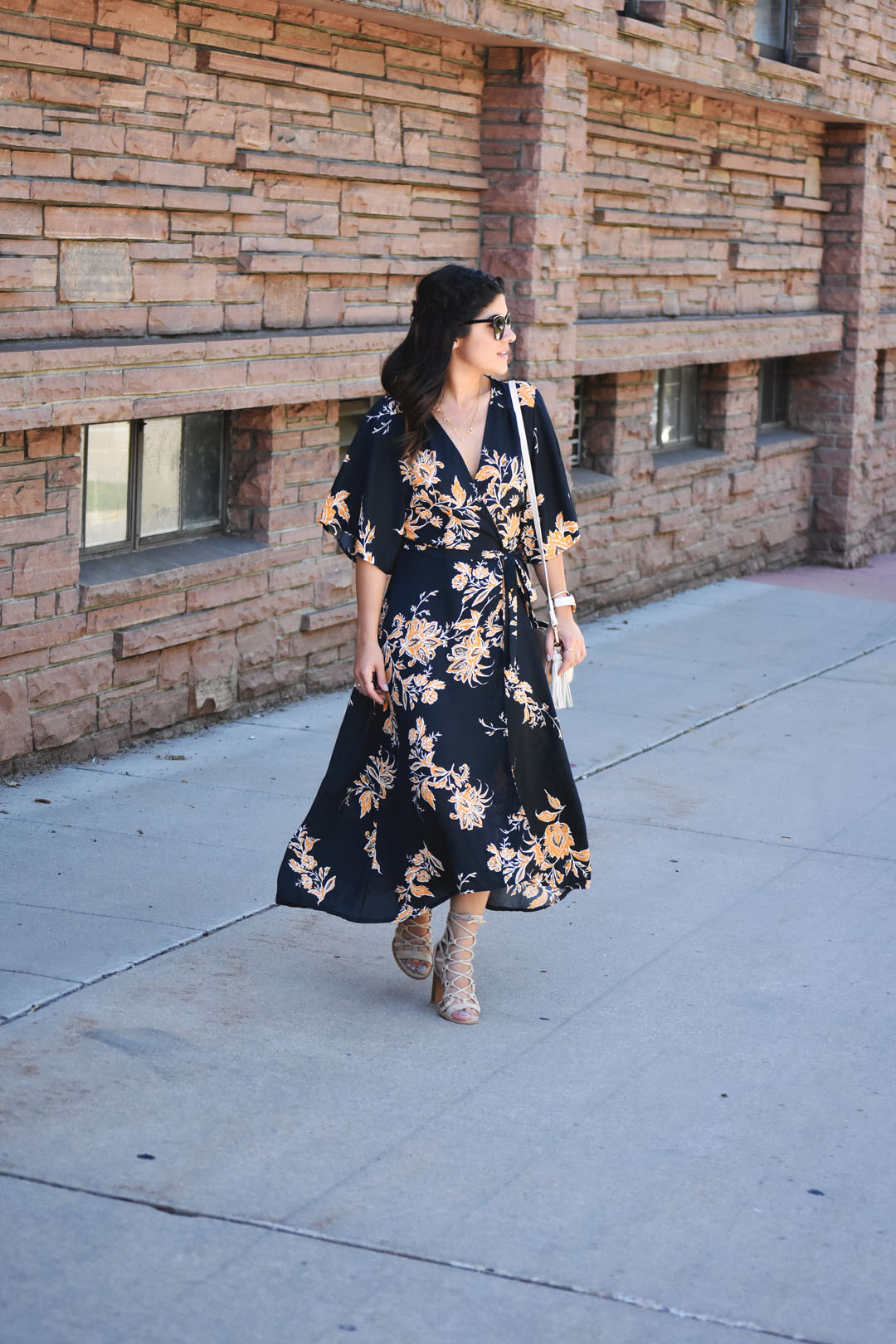 Carolina Hellal of Chic Talk wearing a wrap maxi floral dress, beige lace up sandals, and h&m beige tassle crossbody bag.