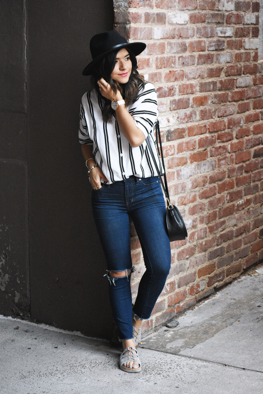 Carolina Hellal of Chic Talk wearing a stripe top, Madewell ripped jeans, and Skechers sandals