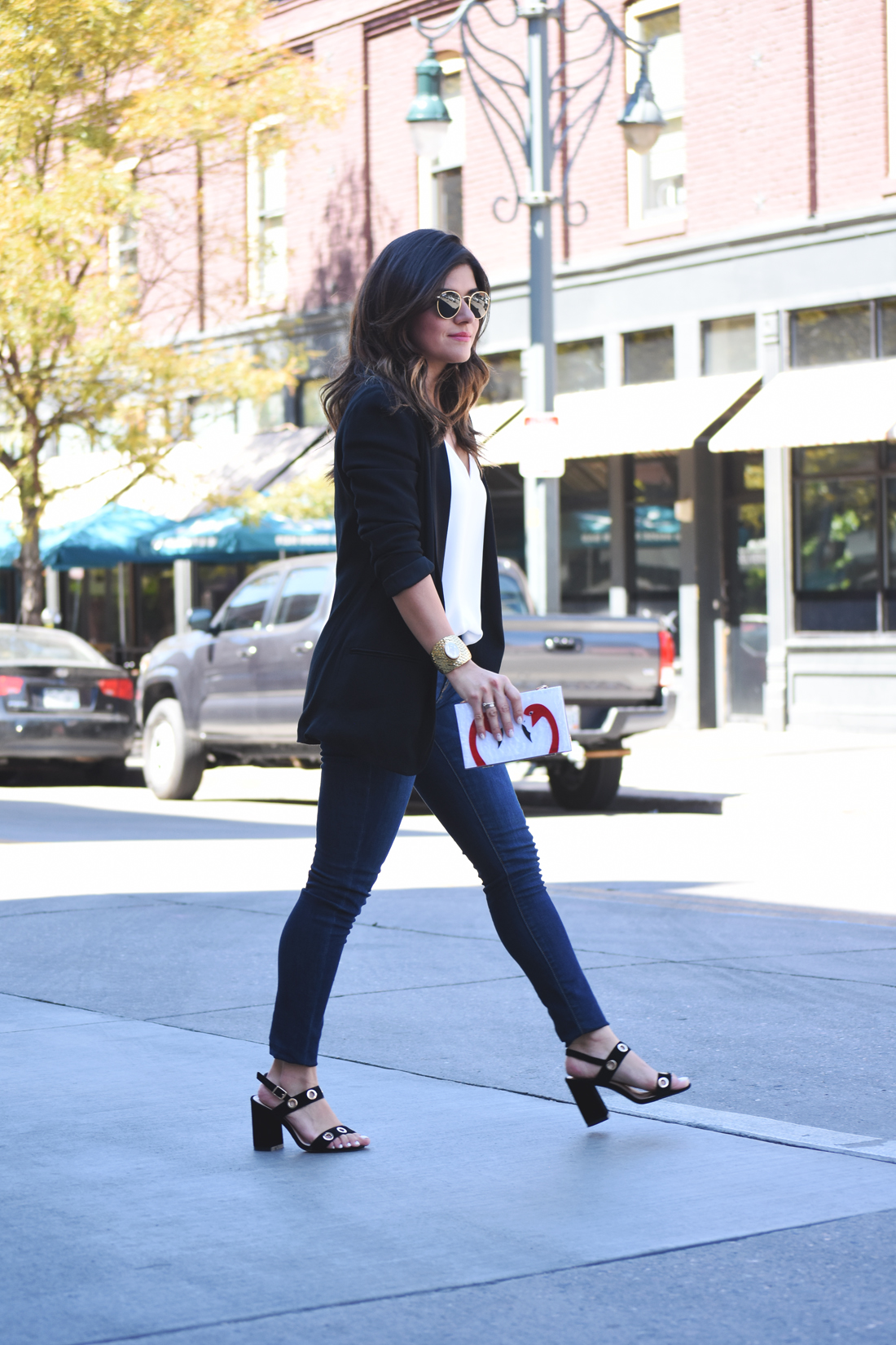 Carolina Hellal of Chic Talk wearing Rayban Rounded sunglasses, an H&M black blazer, a white Topshop top, Public Desire black sandals, and Old Navy jeans.