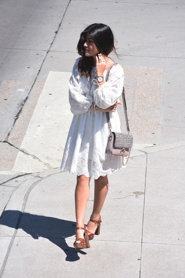 Carolina Hellal of Chic Talk wearing a white summer dress via VIPME, Kendra Scott accessories, and Macy's wooden platform sandals.