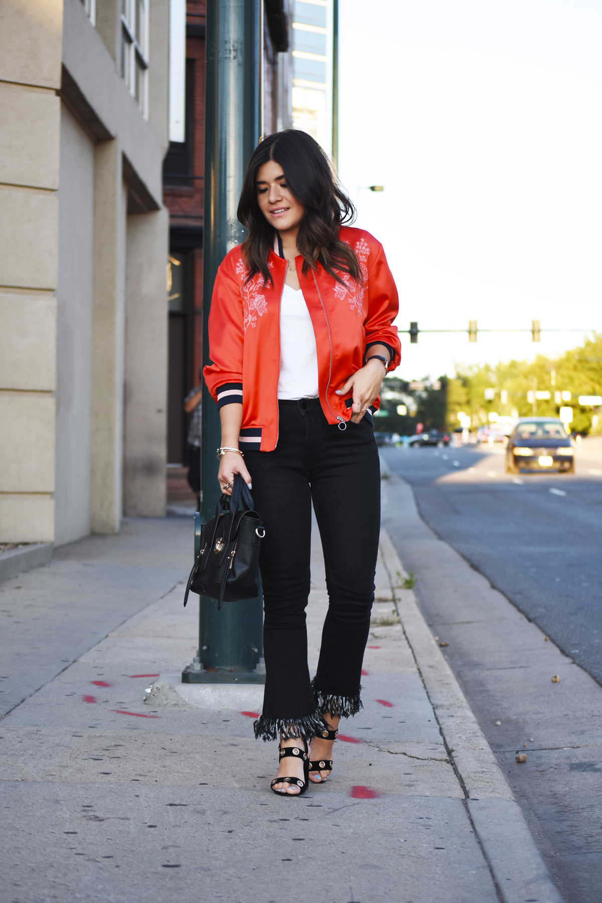 Carolina Hellal of Chic Talk wearing a red H&M Bomber jacket, Dezzal fringed jeans, and Public Desire black sandals