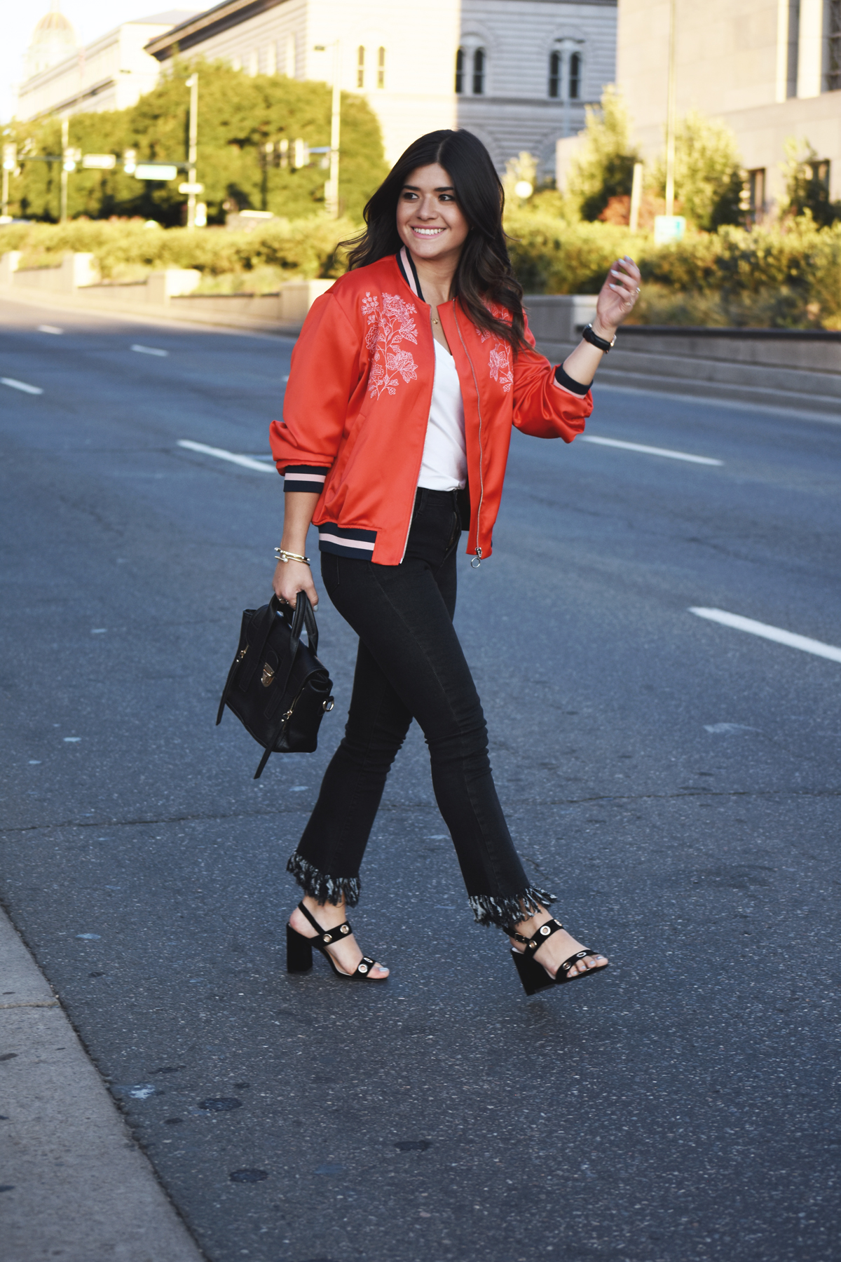 Carolina Hellal of Chic Talk wearing an H&M red bomber jacket, Dezzal fringe jeans, and Public Desire sandals