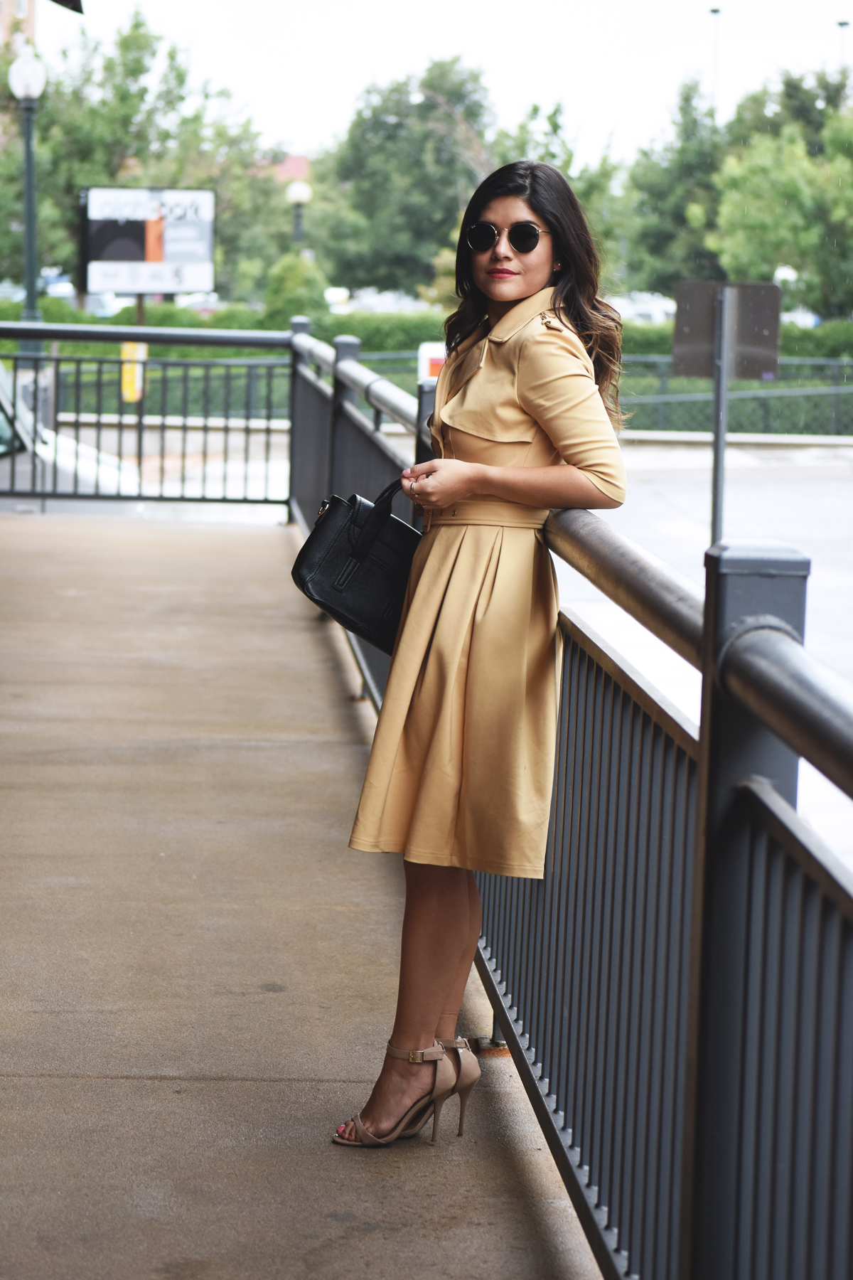 Carolina Hellal of the fashion blog Chic Talk wearing a trench dress via Chicwish, strap sandals, Rayban rounded sunglasses and a black handbag