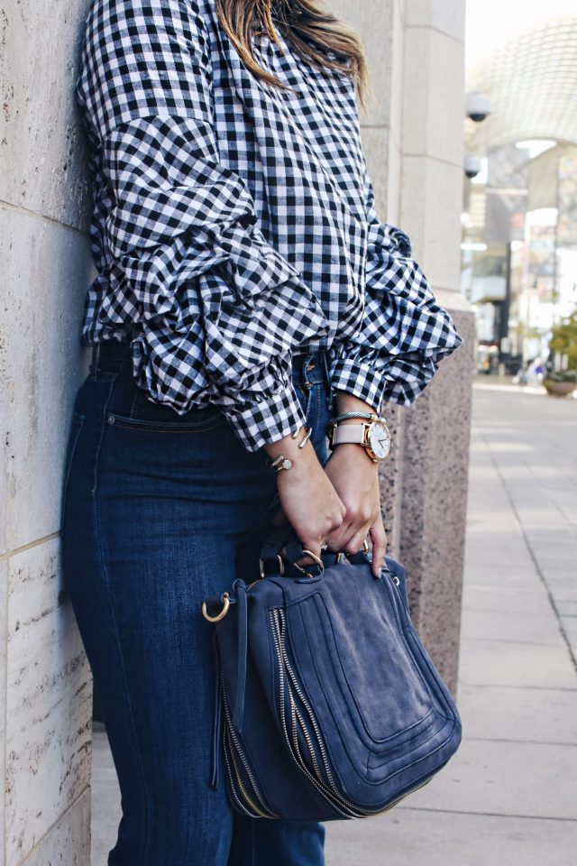 Carolina Hellal of Chic Talk wearing a Gingham top via Shein, Rayban rounded sunglasses, Levi's flare jeans and a Violet Ray suede bag