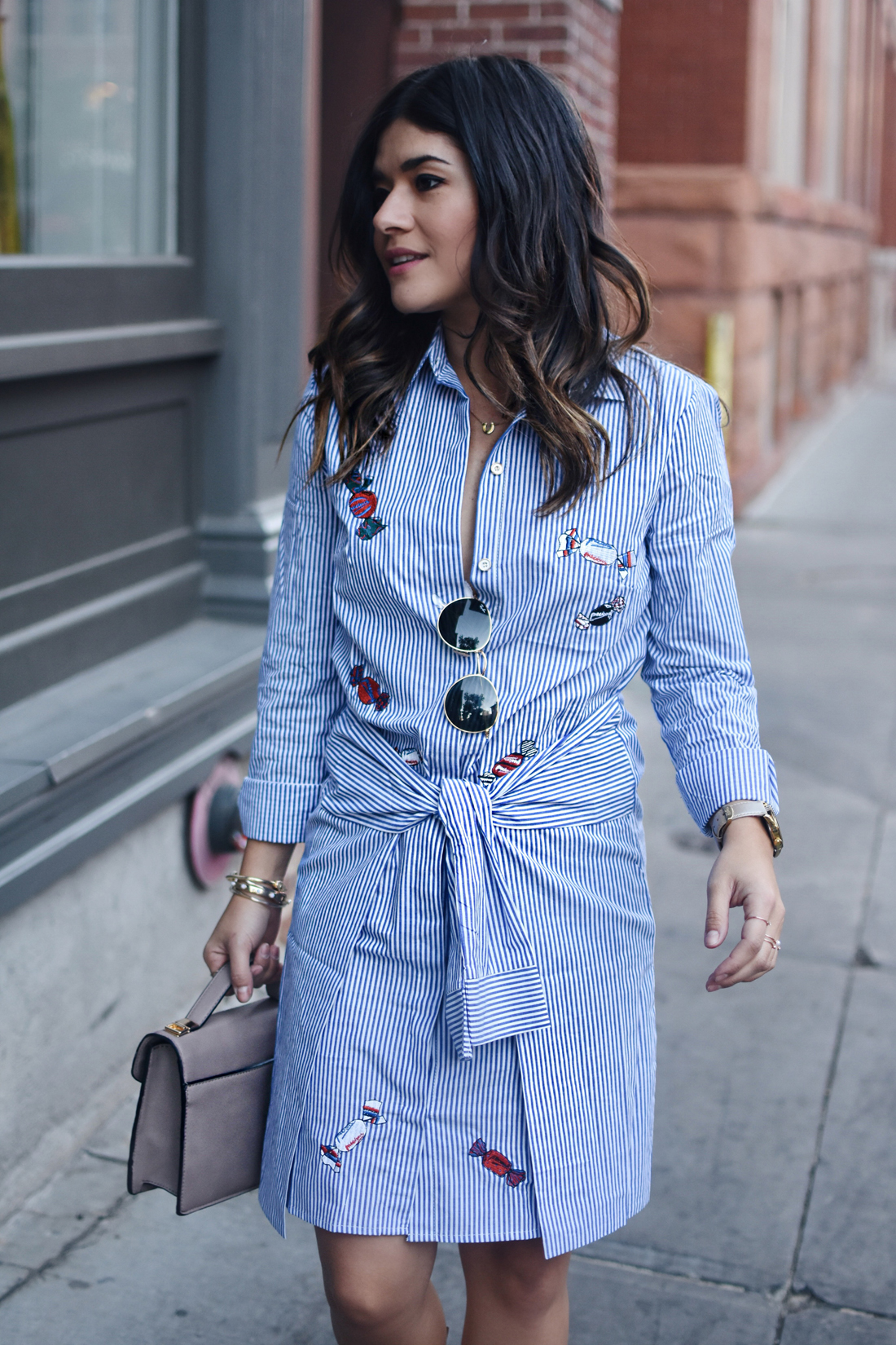 Carolina Hellal of Chic Talk wearing a wrapped stripped dress and Rayban rounded sunglasses