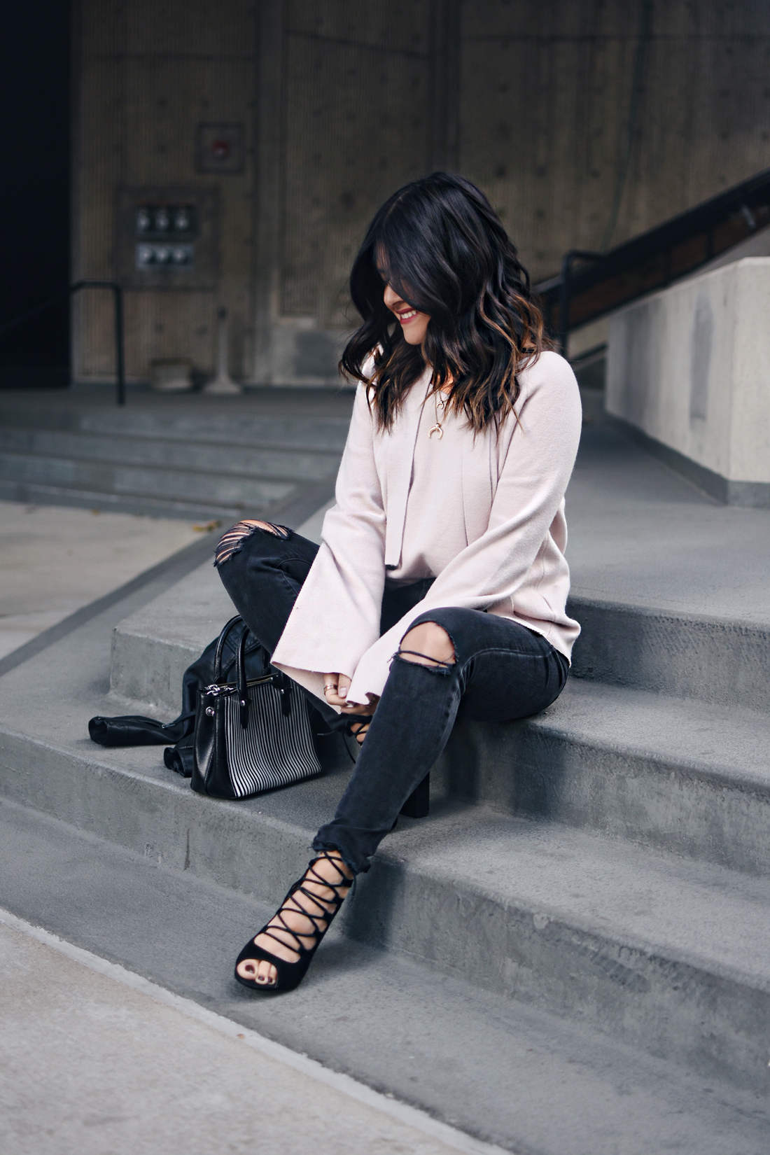 Carolina Hellal of Chic Talk wearing a Chicwish bell sleeve sweater, Madewell ripped jeans, Topshop leather jacket, and Public Desire sandals.