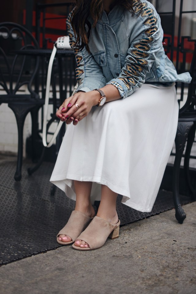 Carolina Hellal of Chic Talk wearing a Free People denim embroidered jacket, The Frye Company white crossbody bag, Donald J Pliner Ellis sandals, and Leith white A line dress via Nordstrom