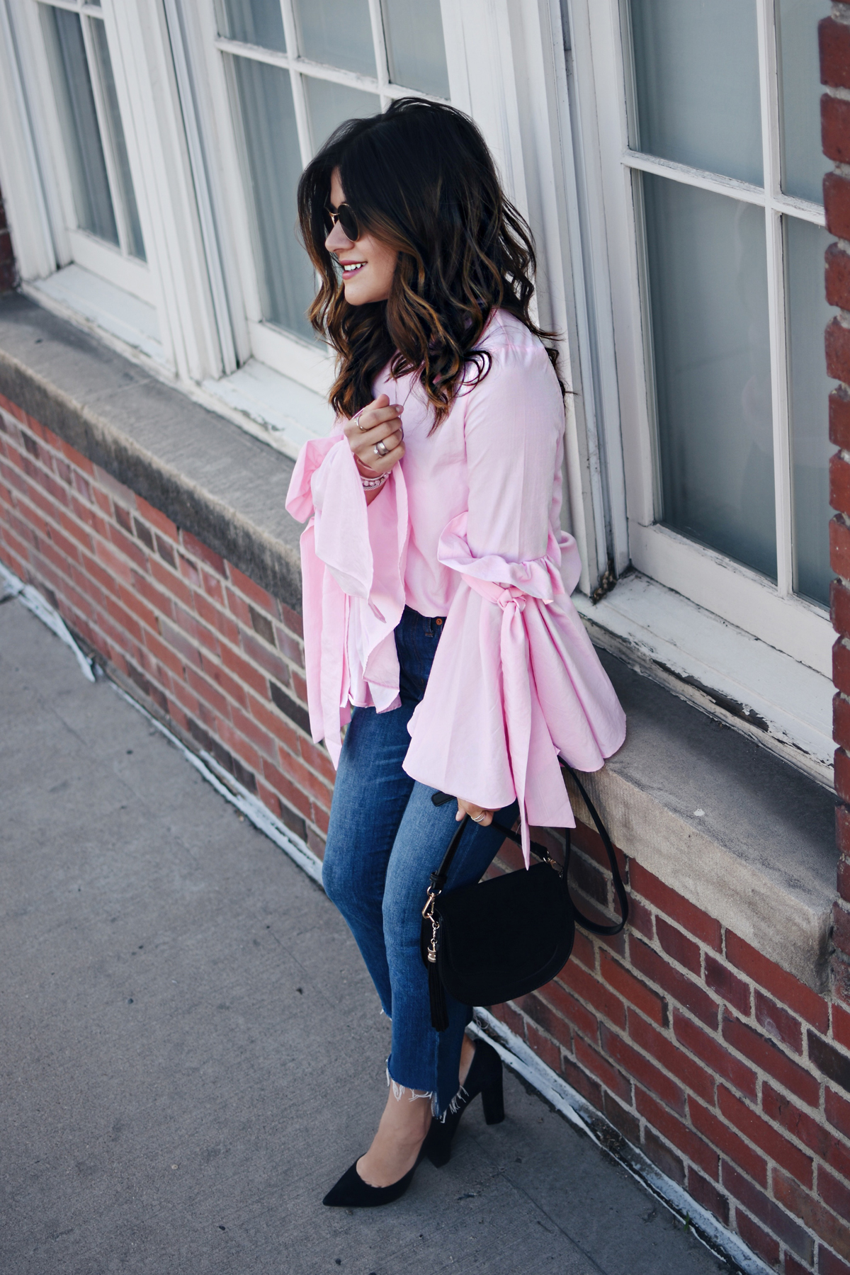 Carolina Hellal of Chic Talk wearing a Chicwish bell sleeve top, Madewell jeans, Steve Madden black pumps, Rebecca Minkoff black purse and Rayban Sunglasses