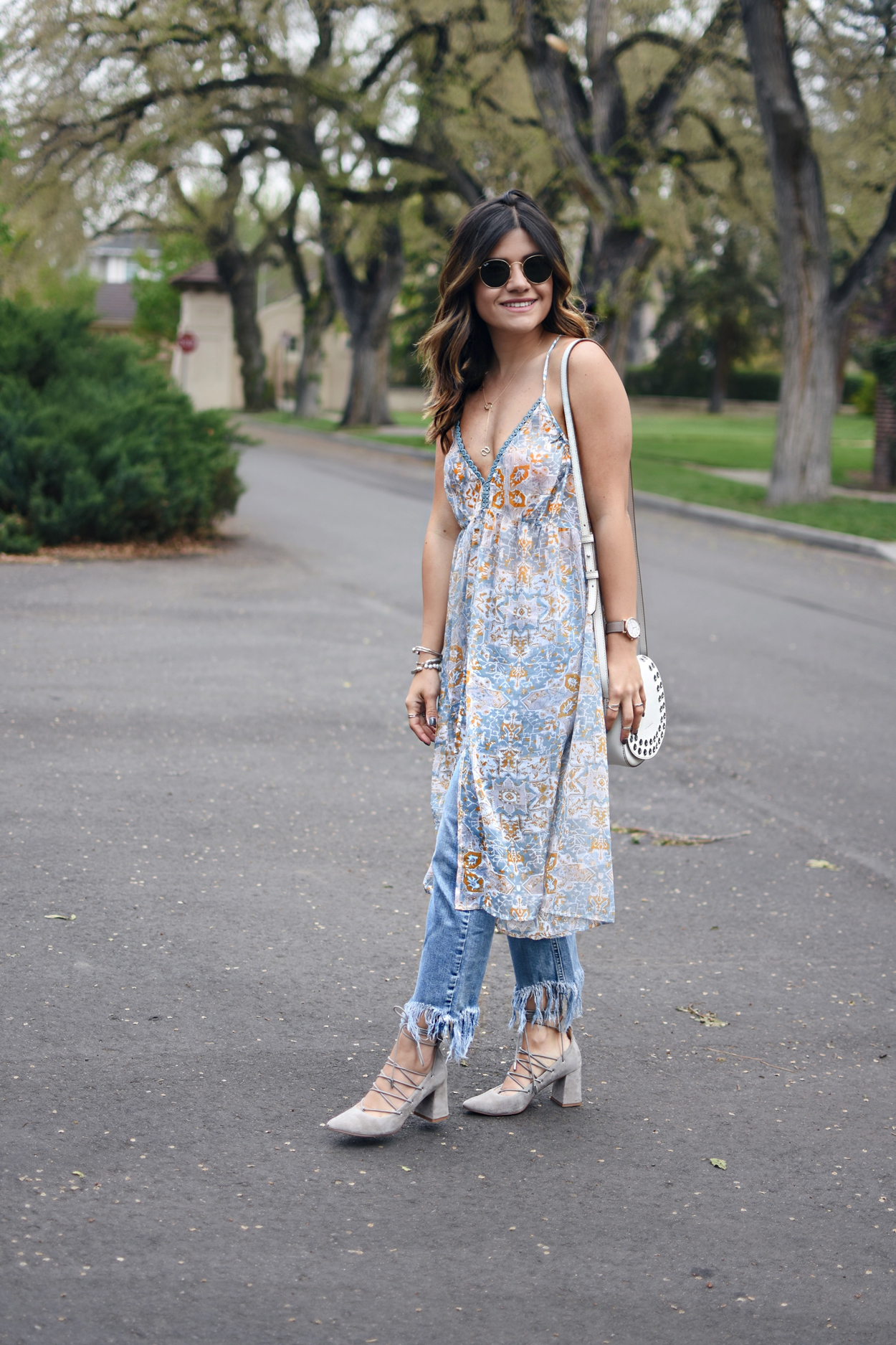 Carolina Hellal of Chic Talk wearing a floral tunic, fringed jeans, lace up heels, Rounded Rayban sunglasses and a white crossbody bag
