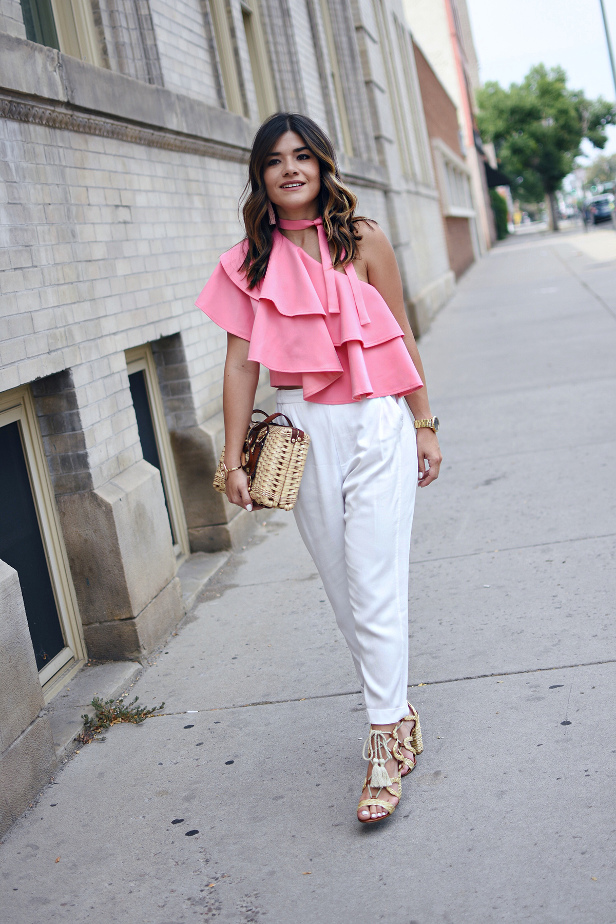 Carolina Hellal of Chic Talk wearing an off the shoulder pink ruffle top with white pants, straw bag and MIA lace up heels