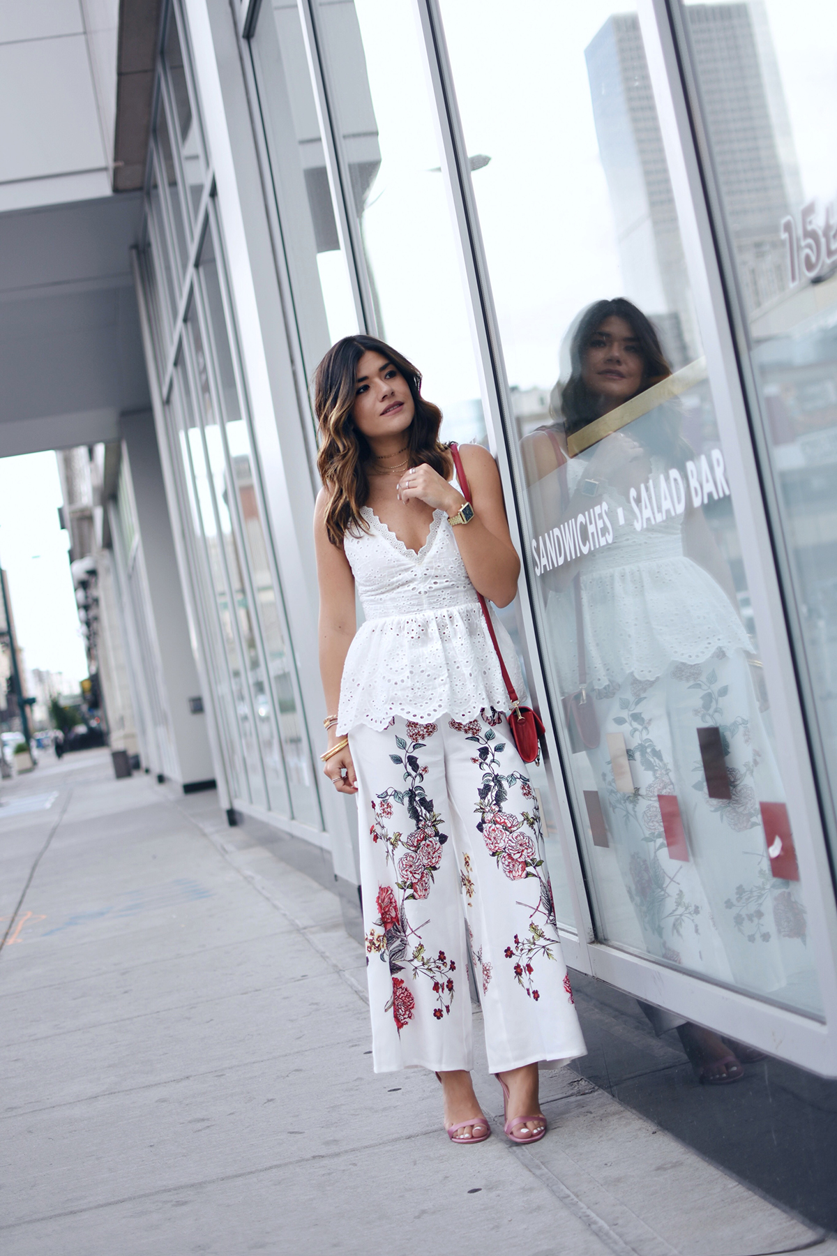 Carolina Hellal of Chic Talk wearing Shein floral pants, white open back top, Public Desire sandals and Moda Luxe bag