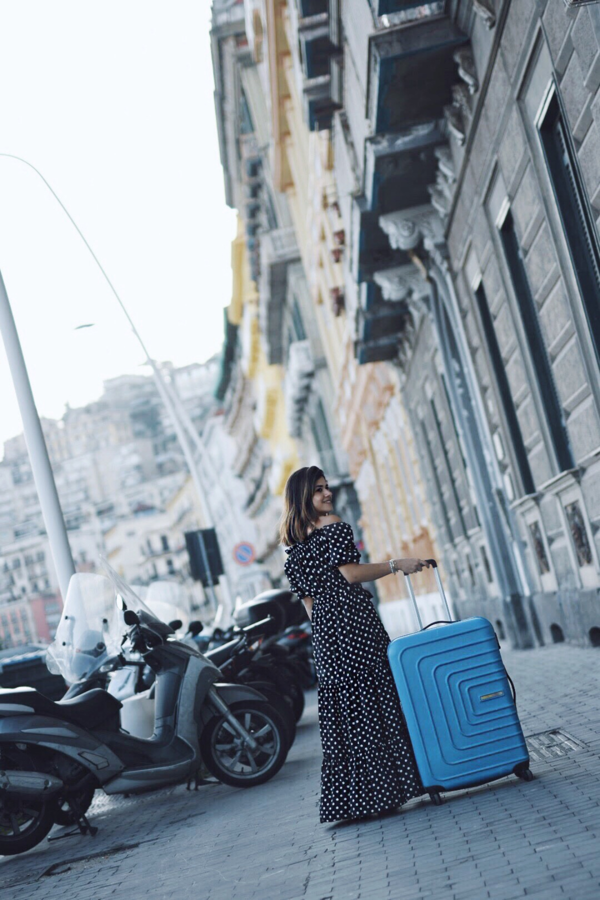 Carolina Hellal of Chic Talk wearing a shein polka dot dress and an American Tourister bag