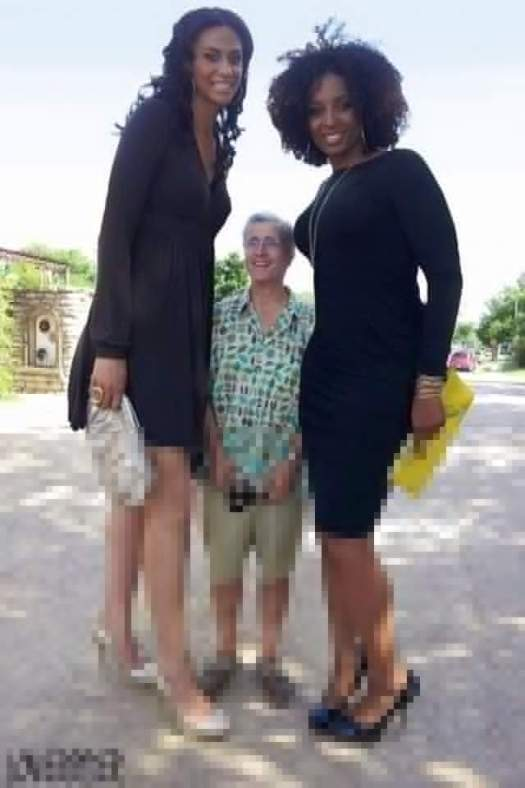 Two tall black beauties towering over a short man