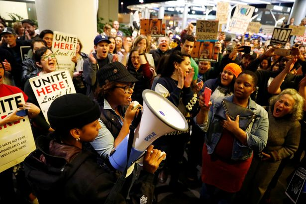 A-protester-announces-a-court-decision-blocking-deportations-as-people-protest-against-US-Presiden