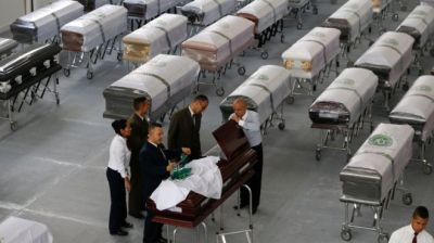 Funeral employees cover a casket, decorated with a Chapecoense soccer team logo, containing the remains of a team member at San Vicente funeral home in Medellin, Colombia, Friday, 2 December 2016.