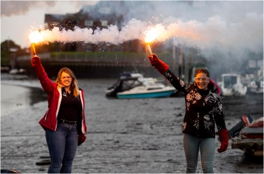 Two women holding up flares in their hands