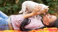 women laying on mat taking chihuahua in her hands