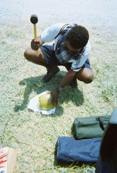 Myles hammering a coconut