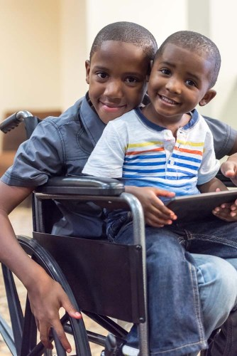 Black/African-American child in wheelchair playing with his little brother