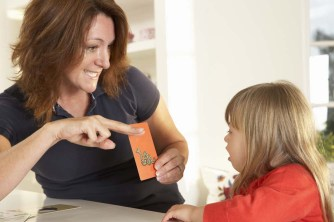 teacher working with young girl while holding a flashcard