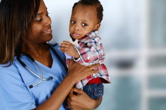 Black/African-American doctor holding a baby in a plaid shirt