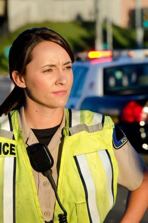 female police officer standing in front of a police vehicle