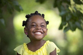 Black/African-American preschooler in bright yellow top grins happily.