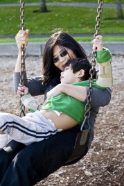 Mom with Latino boy with disabilities in her lap swinging on a swing
