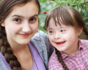 Young white woman sitting next to little girl with down syndrome
