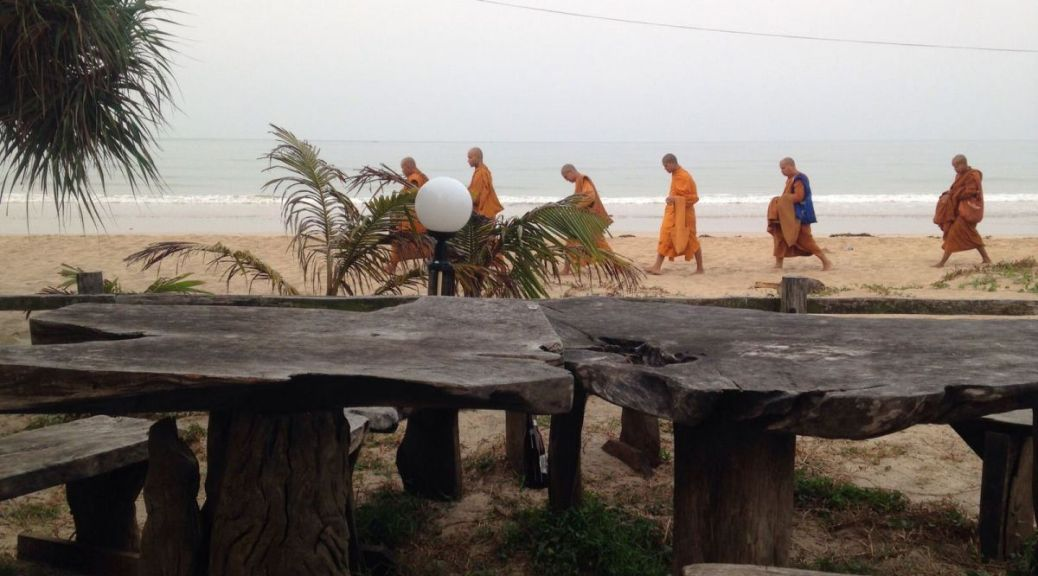 Monks walking on chao lao beach Thailand