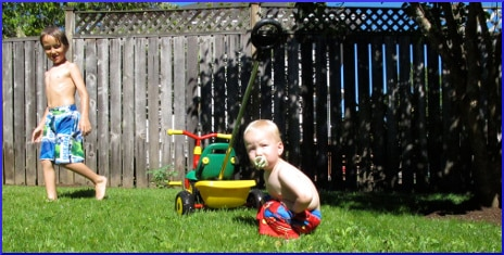 [two small boys playing in a backyard]