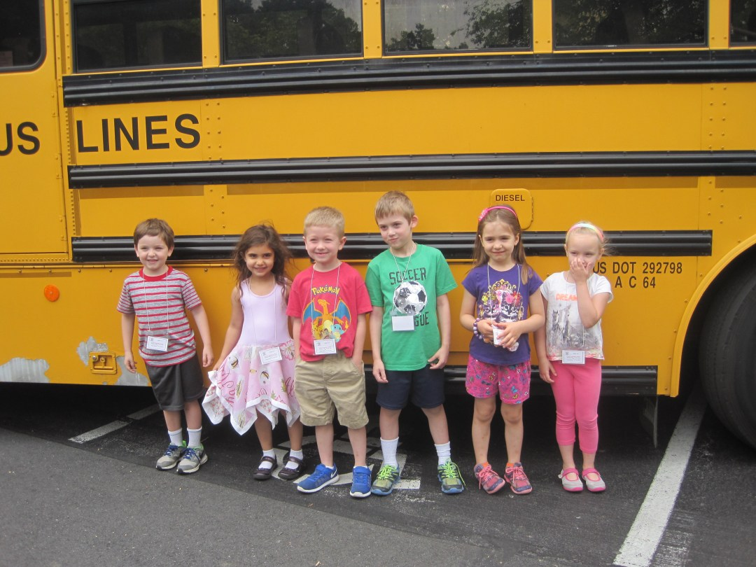 Children standing in front of a school bus on a field trip.