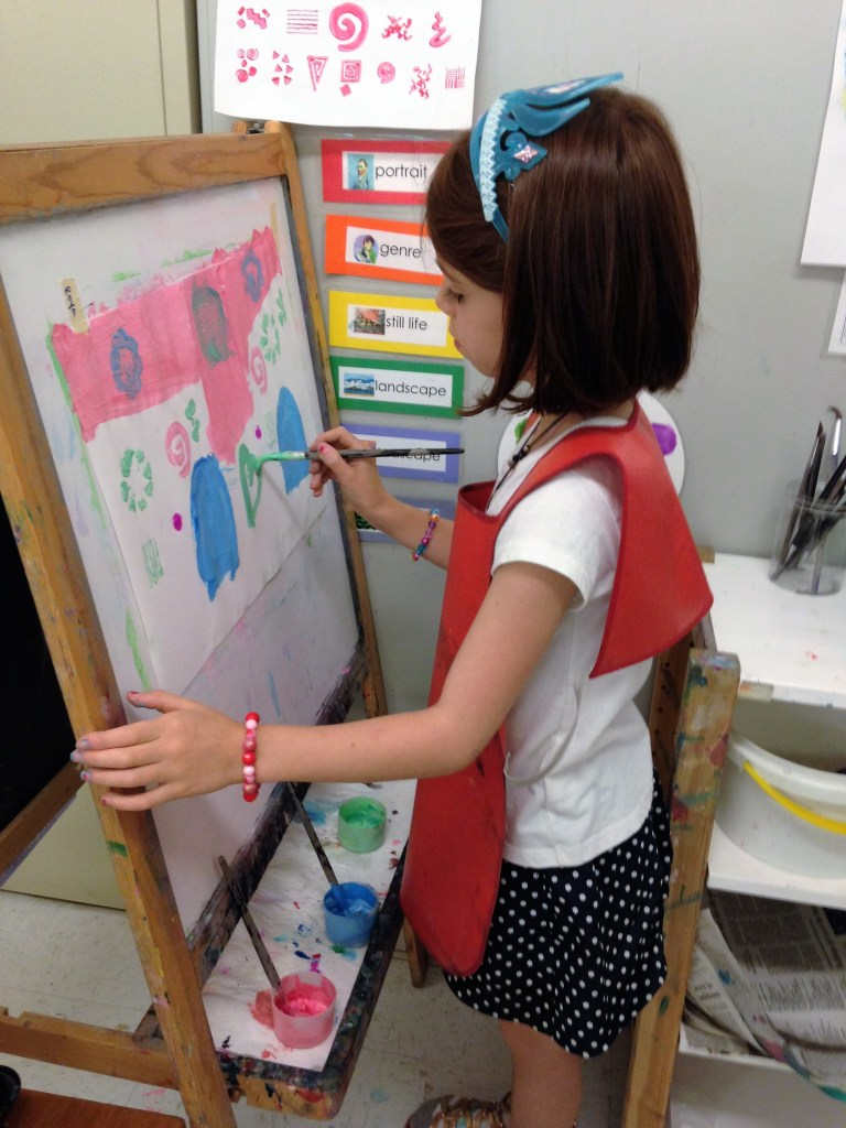 A child paints at the easel. Motivating children without praise and rewards